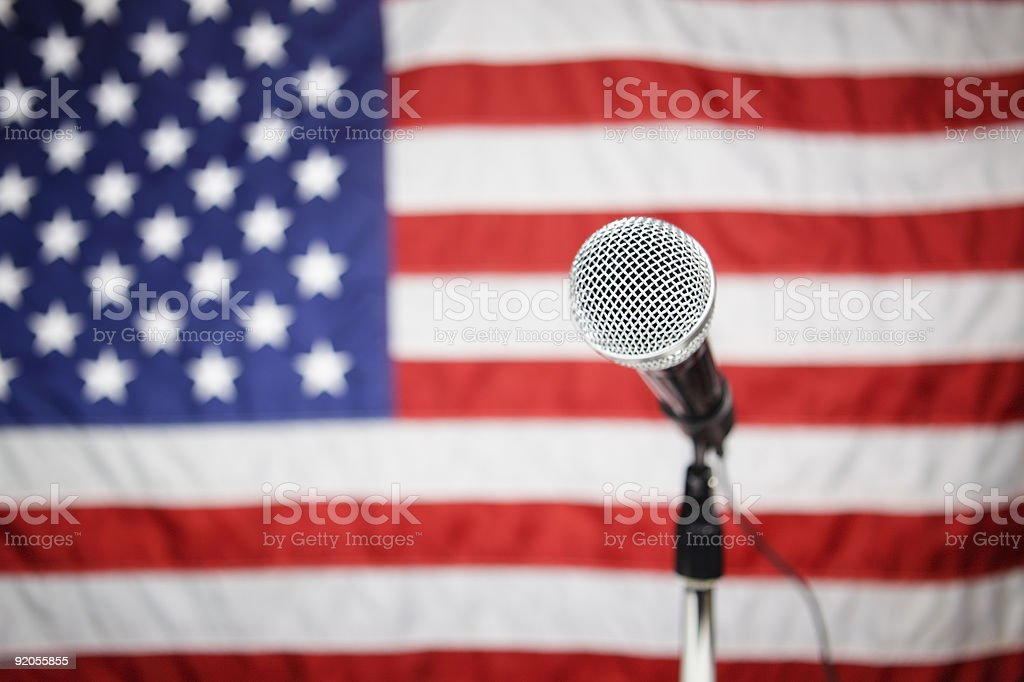 A microphone with an American flag in the background stock photo
