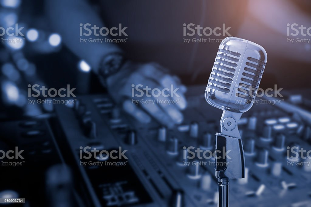 Microphone with Blurred hand of dj on turntable stock photo