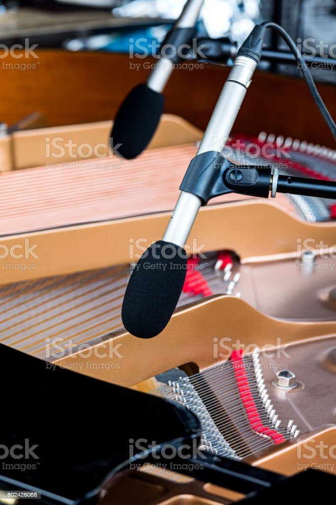 microphones above grand piano with selective focus on one of them stock photo