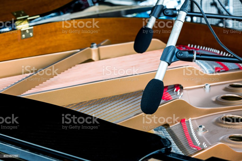 microphones above the strings of black grand piano with raised lid stock photo