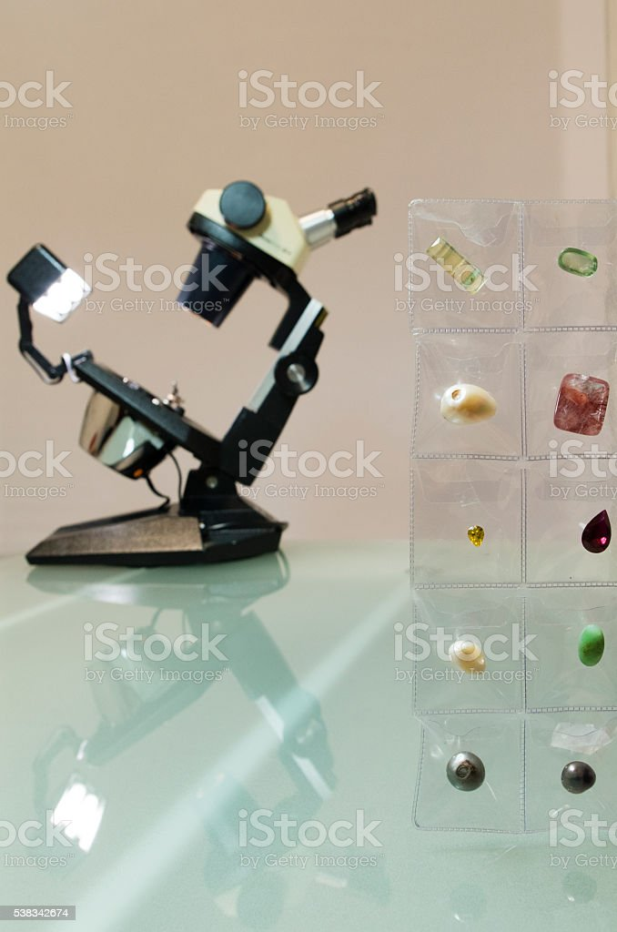Microscope and collection of natural gems and pearls stock photo