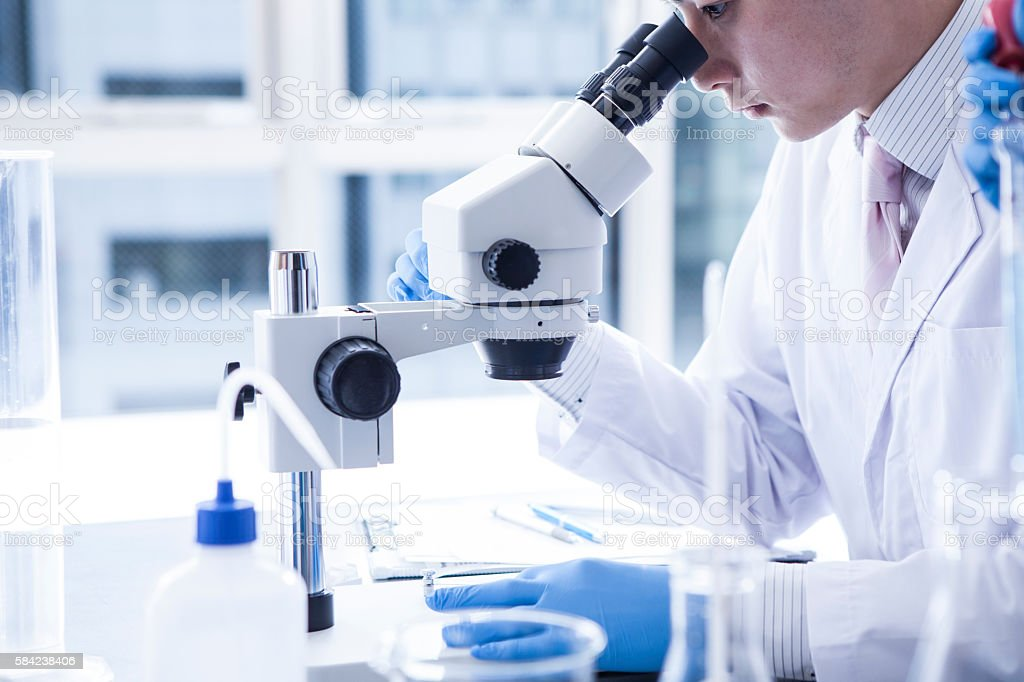 Microscope and male researcher. stock photo