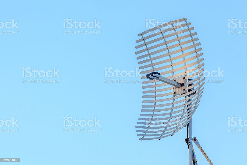 Microwave antenna dish on clear blue sky background. stock photo