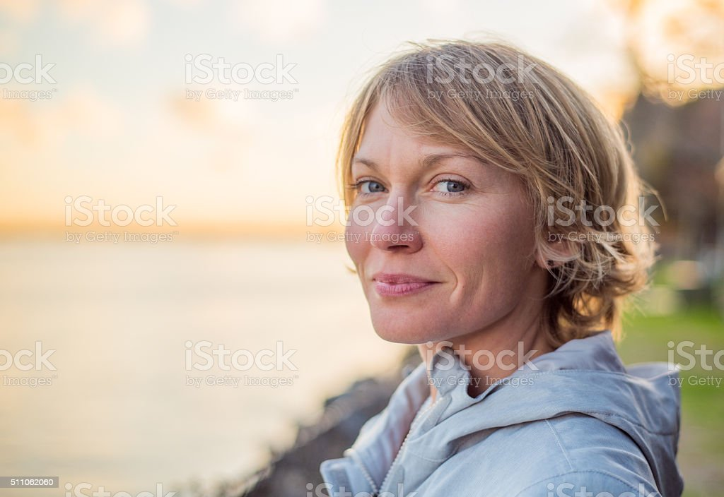 Mid 30's Woman with strong smile at sunset. stock photo
