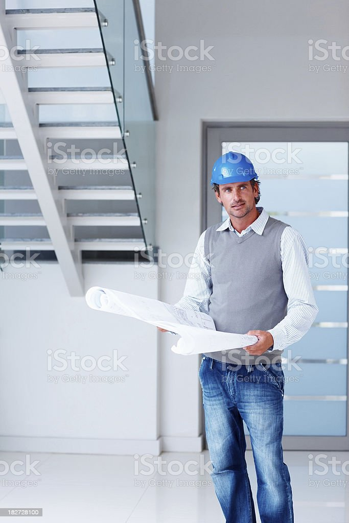 Mid adul architect with blueprints of a new project royalty-free stock photo