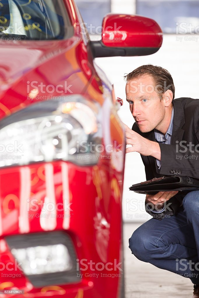 Mid adult appraiser looking at red car, estimate for fix stock photo