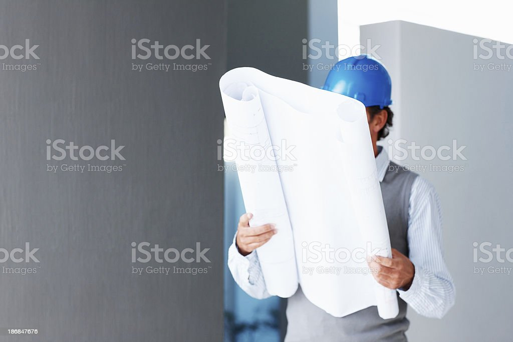 Mid adult architect with blueprints of a new project royalty-free stock photo