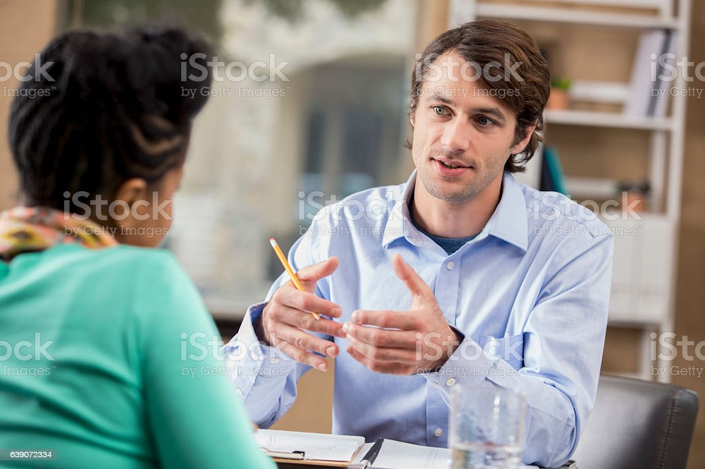 Mid adult businessman interviews potential employee stock photo