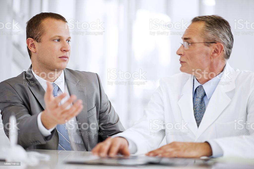 Mid adult businessman talking to a mature doctor. royalty-free stock photo