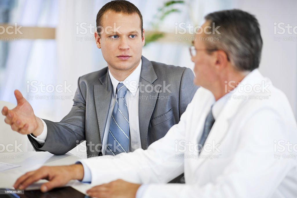 Mid adult businessman talking to a mature doctor. stock photo
