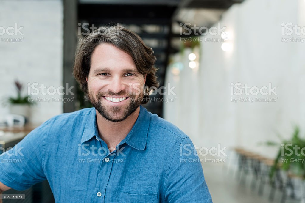 Mid adult businessman with beard smiling towards camera, portrait stock photo
