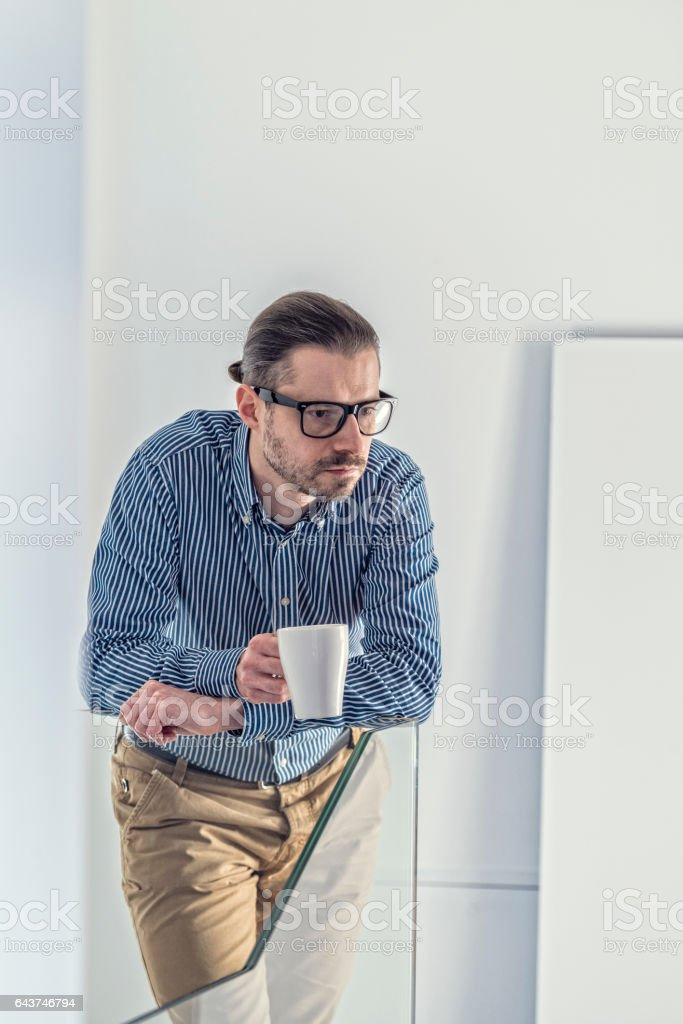 Mid adult businessperson in blue shirt is standing, holding mug stock photo