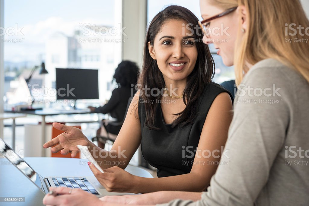 Mid adult businesswoman listening to female colleague in office stock photo