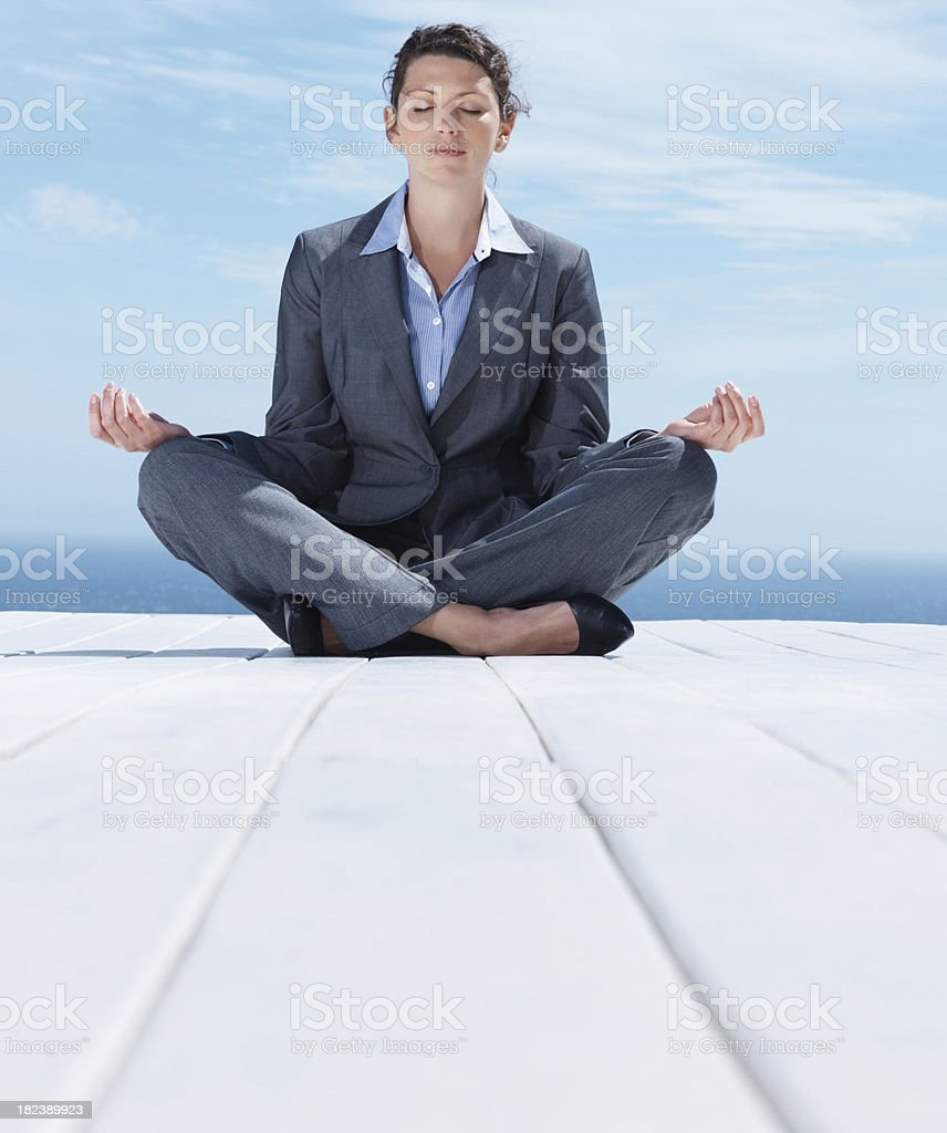 Mid adult businesswoman sitting in lotus position outdoors royalty-free stock photo