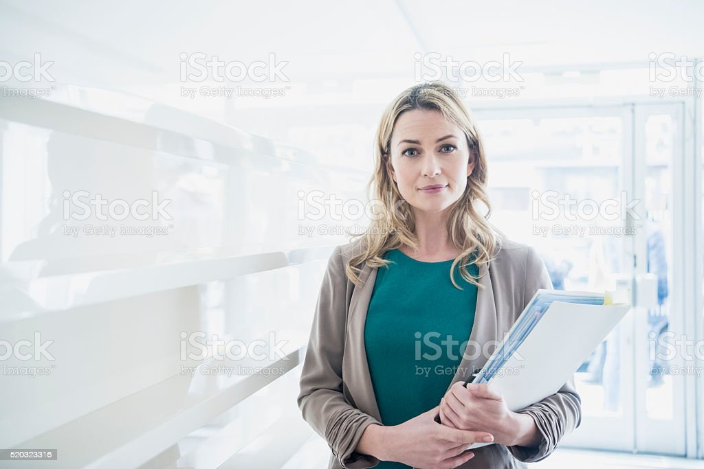 Mid adult businesswoman with paperwork, portrait stock photo