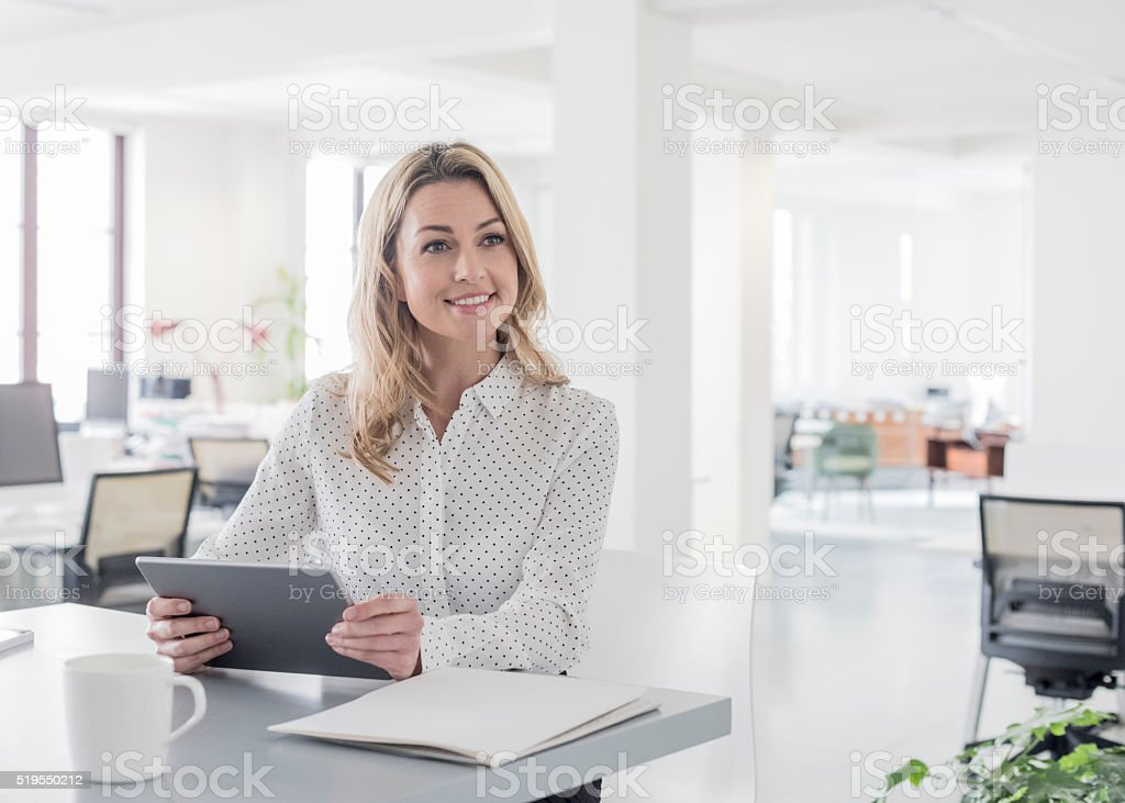 Mid adult businesswoman with tablet, looking away stock photo