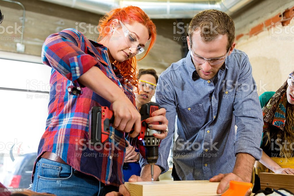 Mid adult Caucasian woman uses power drill in makerspace stock photo