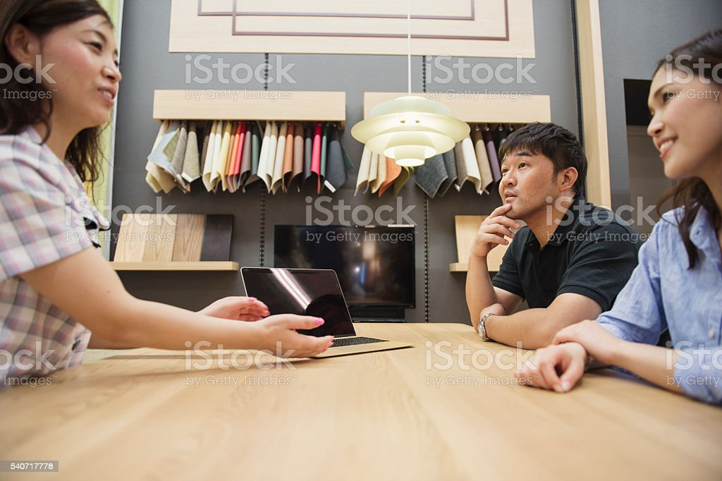 Mid adult couple consulting the staff in Interior shop. stock photo