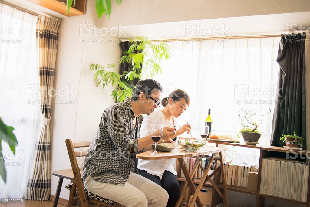 Mid adult couple eat lunch with wine stock photo