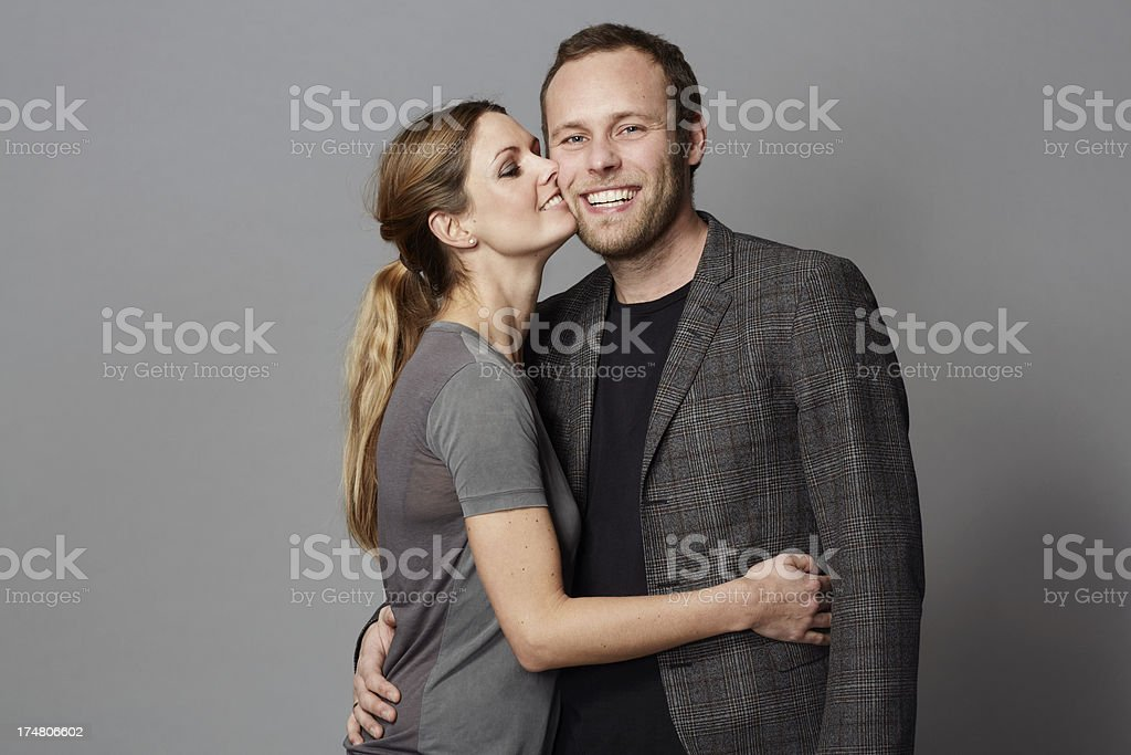 Mid adult couple embracing against grey background royalty-free stock photo