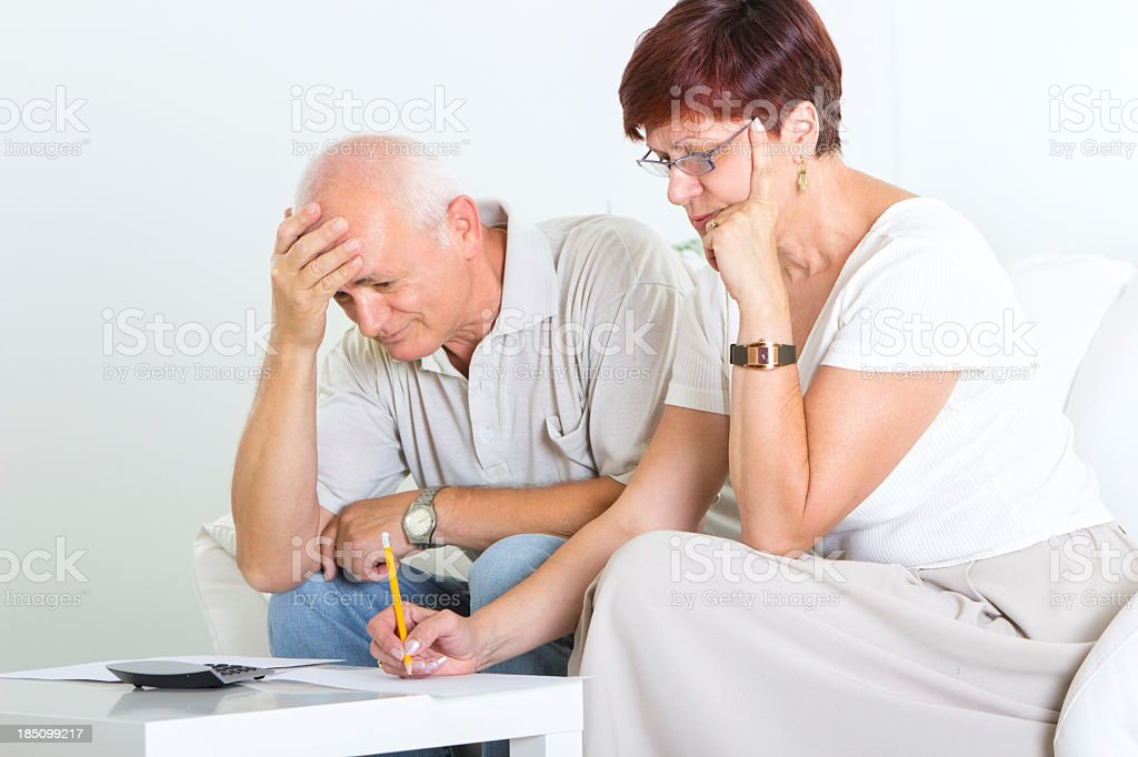 Mid adult couple examining out financial documents stock photo
