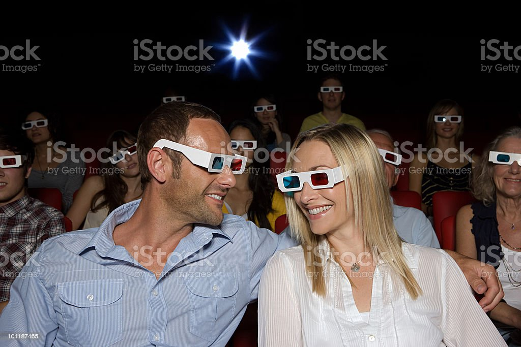 Mid adult couple in movie theater royalty-free stock photo
