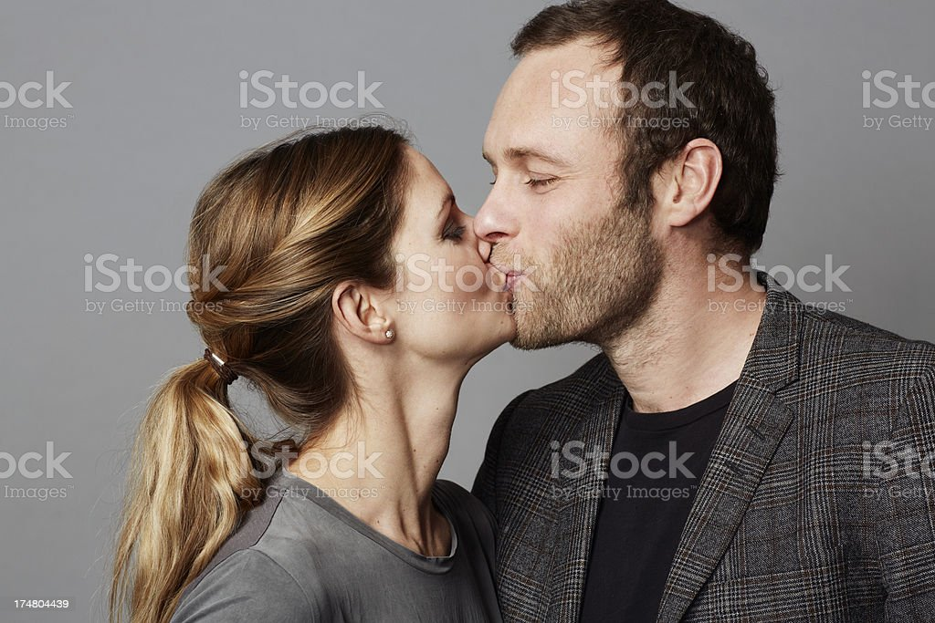 Mid adult couple kissing against grey background royalty-free stock photo