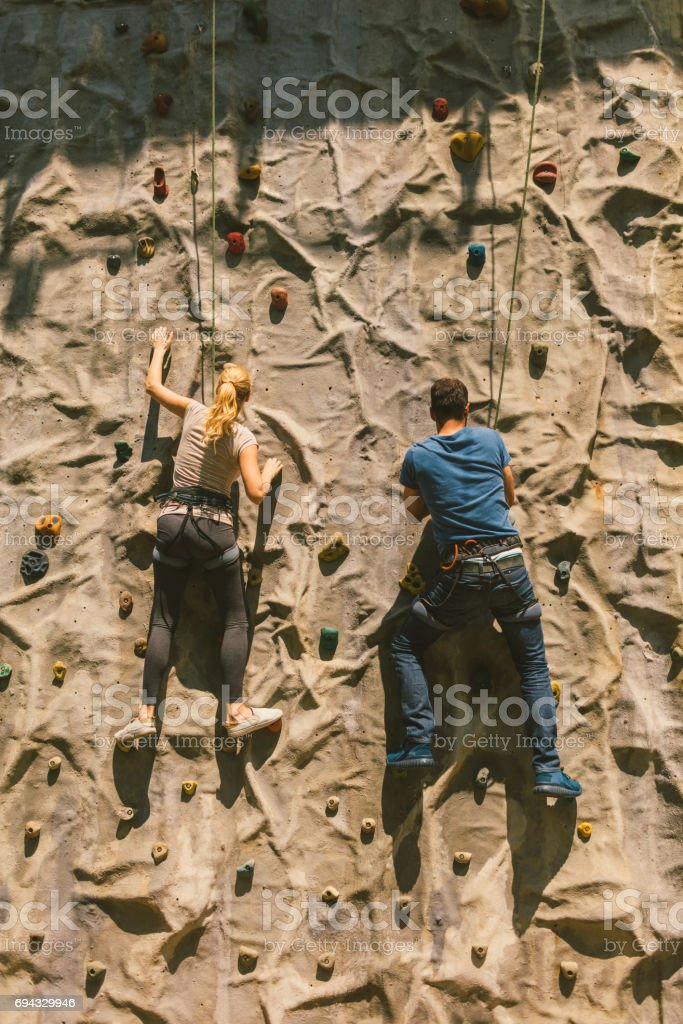 Mid adult couple on free climbing stock photo
