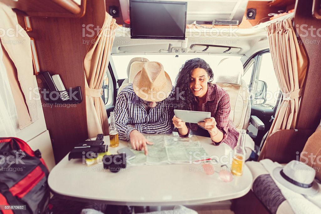 Mid adult couple planning road trip in campervan stock photo
