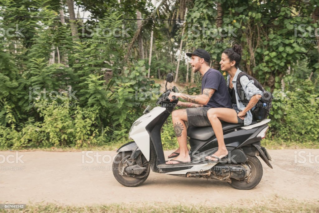 Mid adult couple riding moped through forest, side view stock photo
