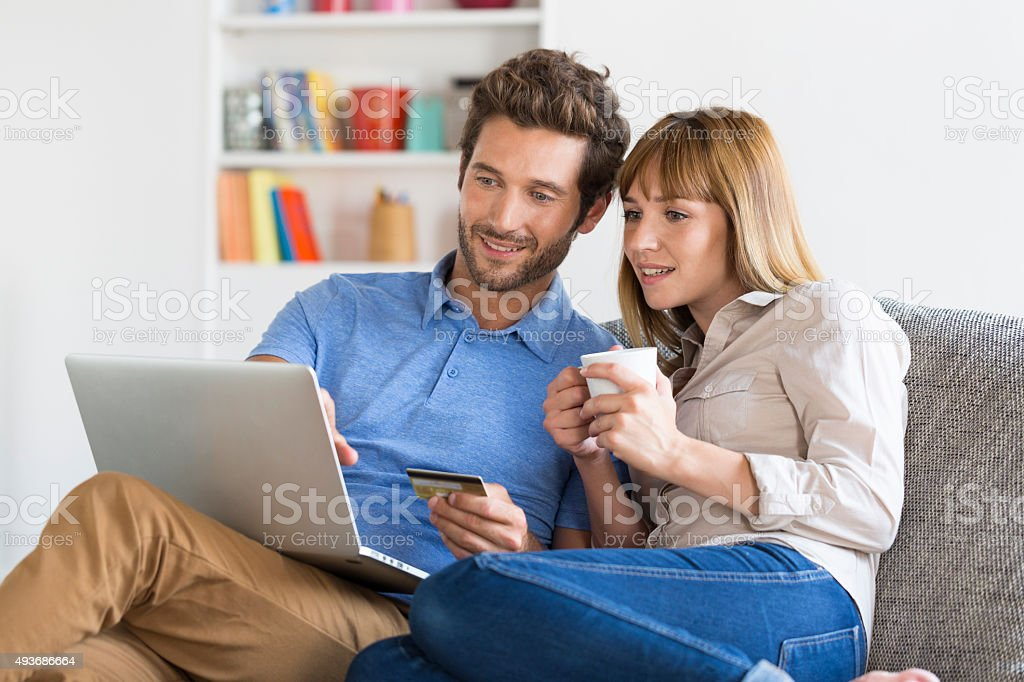 Mid adult couple shopping using laptop and credit card stock photo