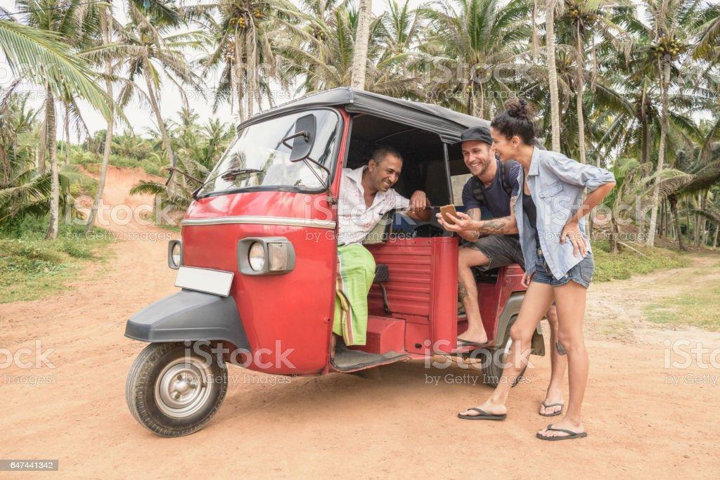 Mid adult couple talking to rickshaw driver, Sri Lanka stock photo