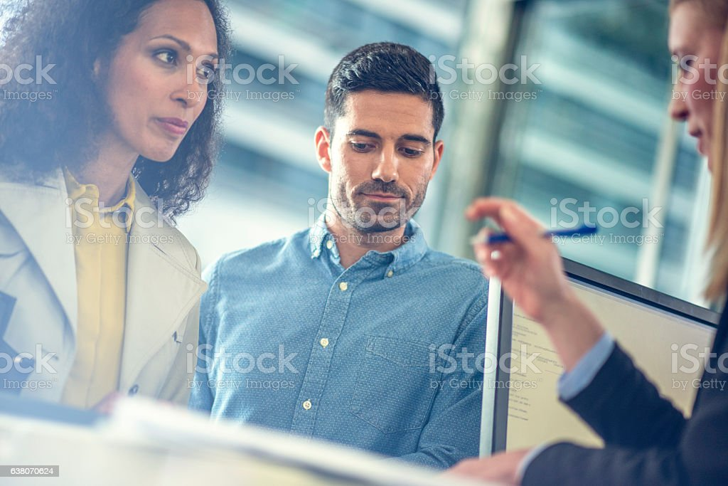 Mid adult couple talking to travel agent stock photo