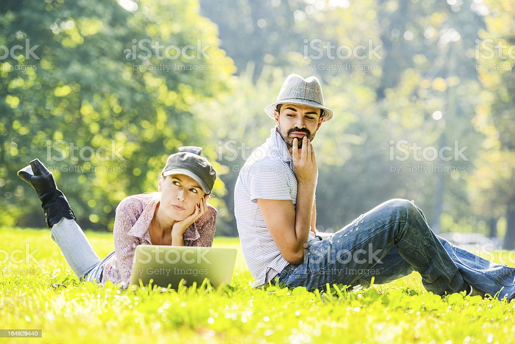 Mid Adult couple using laptop and digital tablet outdoors stock photo