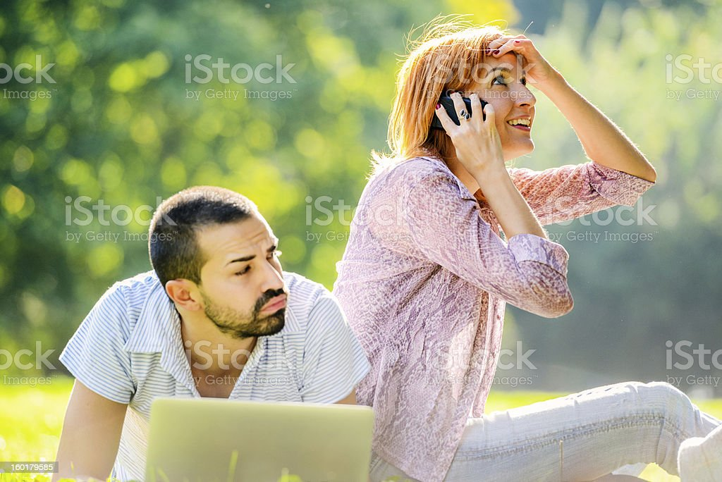 Mid Adult Couple Using laptop outdoors stock photo