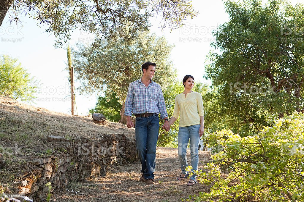 Mid adult couple walking down rural lane on holiday royalty-free stock photo