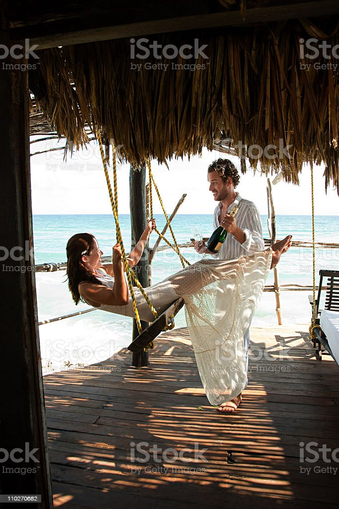 Mid adult couple with champagne, woman on swing stock photo