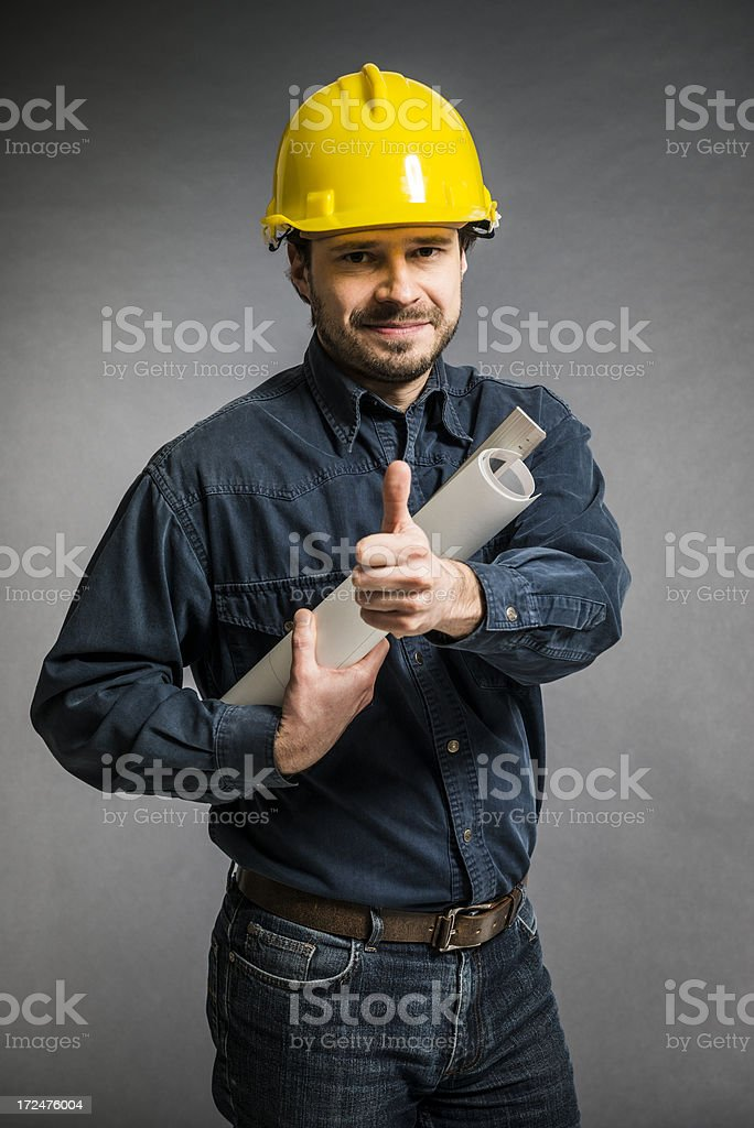 Mid Adult engineer with yellow helmet, blueprint against concrete wall royalty-free stock photo