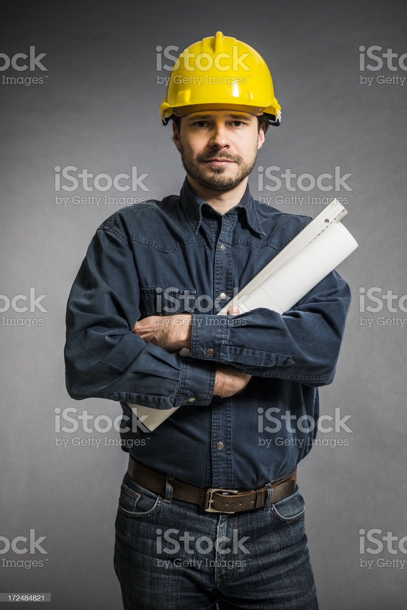 Mid Adult engineer with yellow helmet, blueprint against gray wall royalty-free stock photo