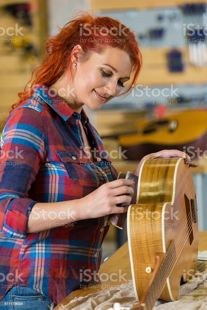 Mid adult female hipster repairs acoustic guitar in music store stock photo