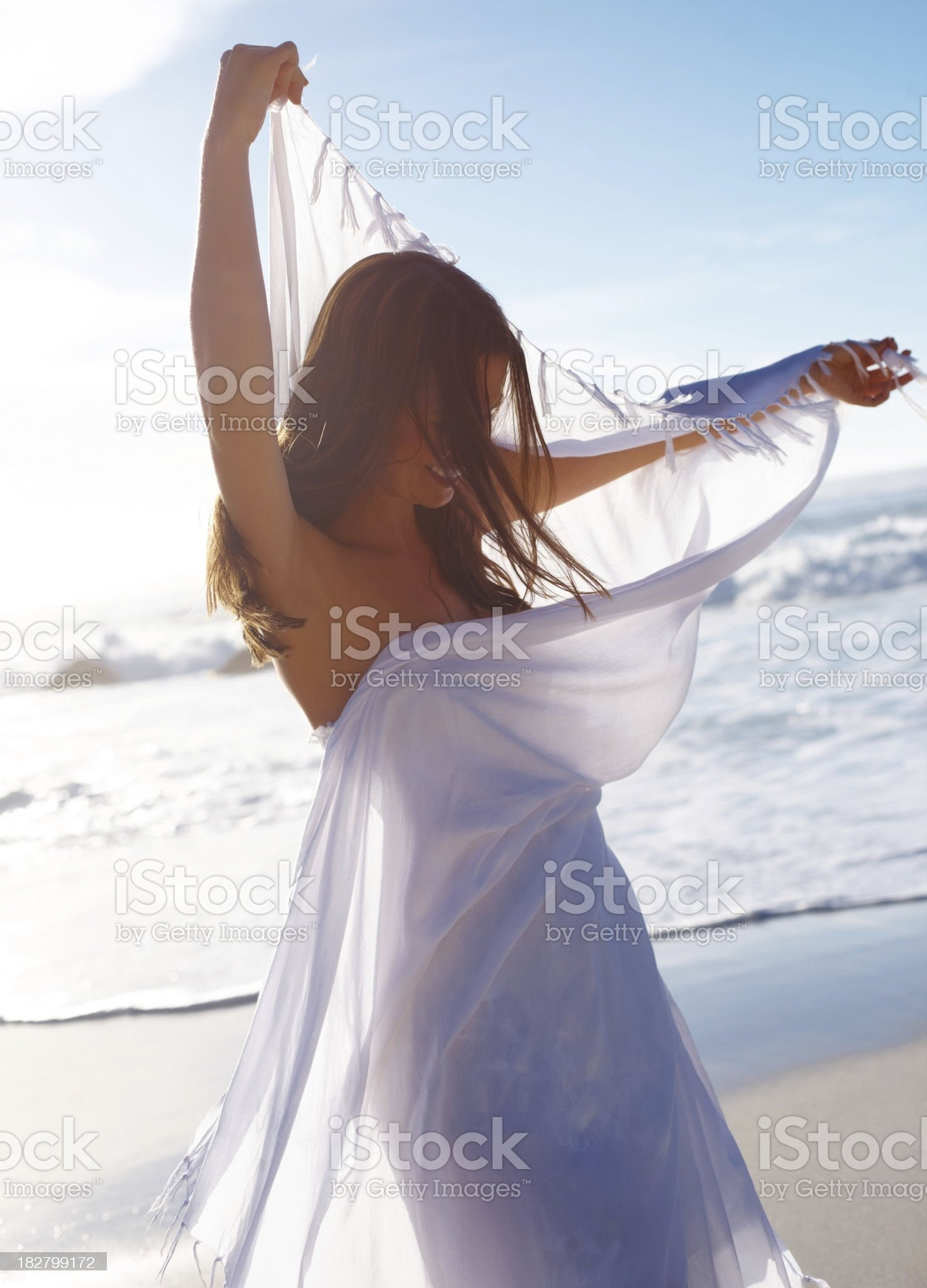 Mid adult female holding a stole while standing on beach royalty-free stock photo