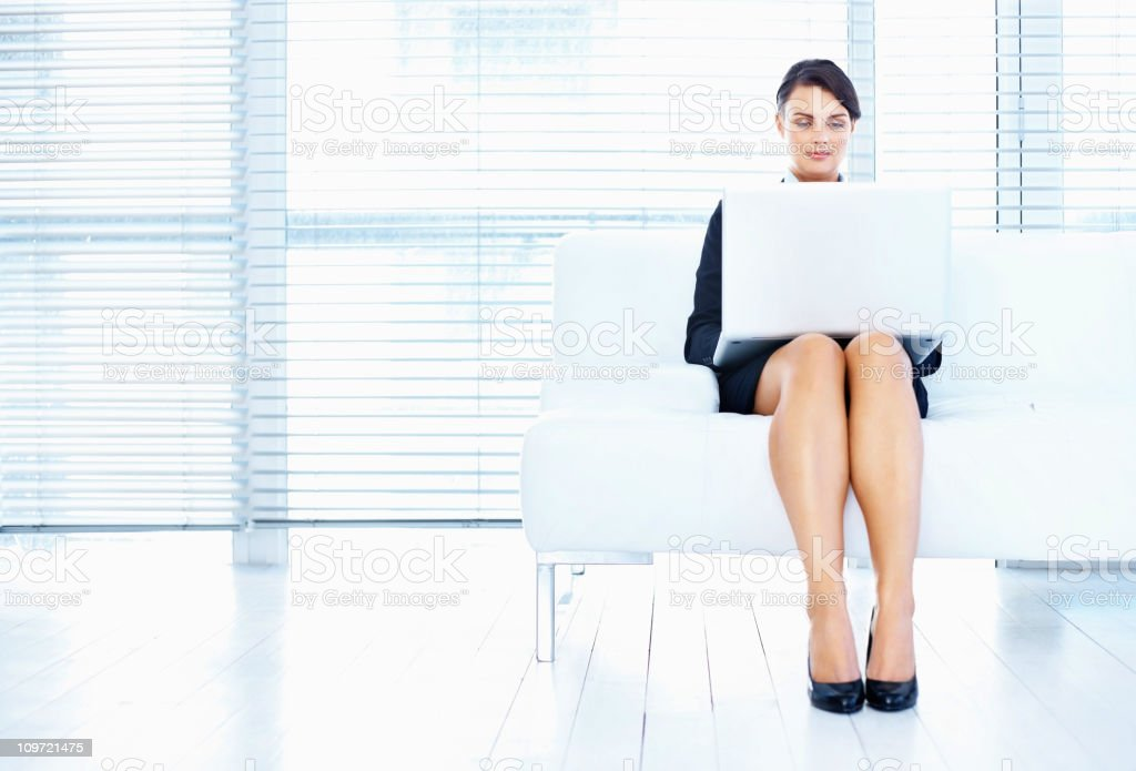 Mid adult female using a laptop while sitting on couch royalty-free stock photo