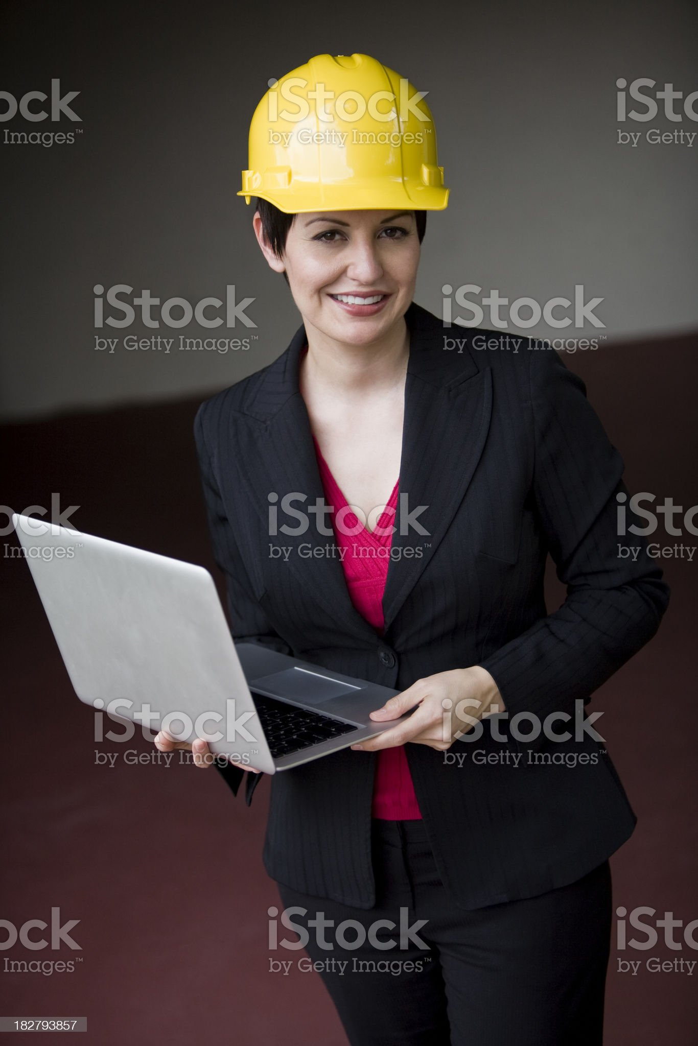 Mid adult female wearing suit with laptop and hard hat royalty-free stock photo