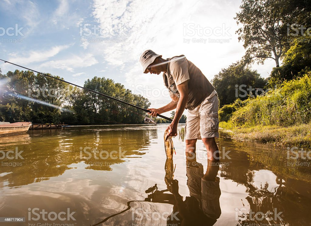 Mid adult fisherman caught a common carp on the river. stock photo