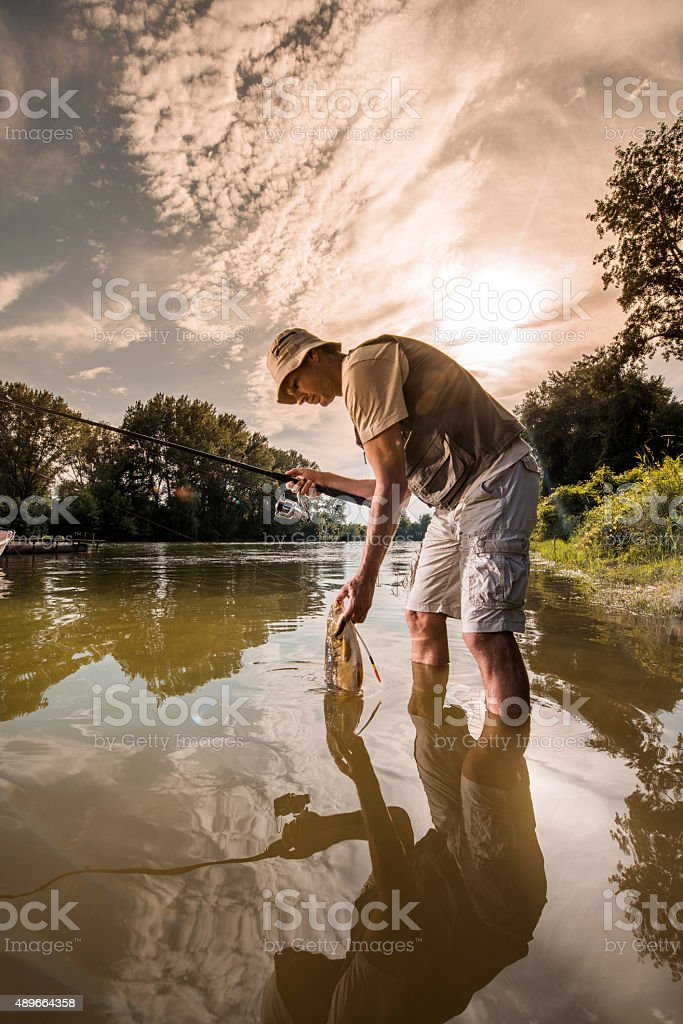 Mid adult fisherman holding his catch in the river. stock photo