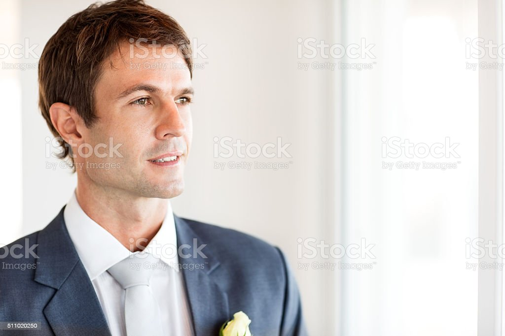 Mid Adult Groom Looking Away At Home stock photo