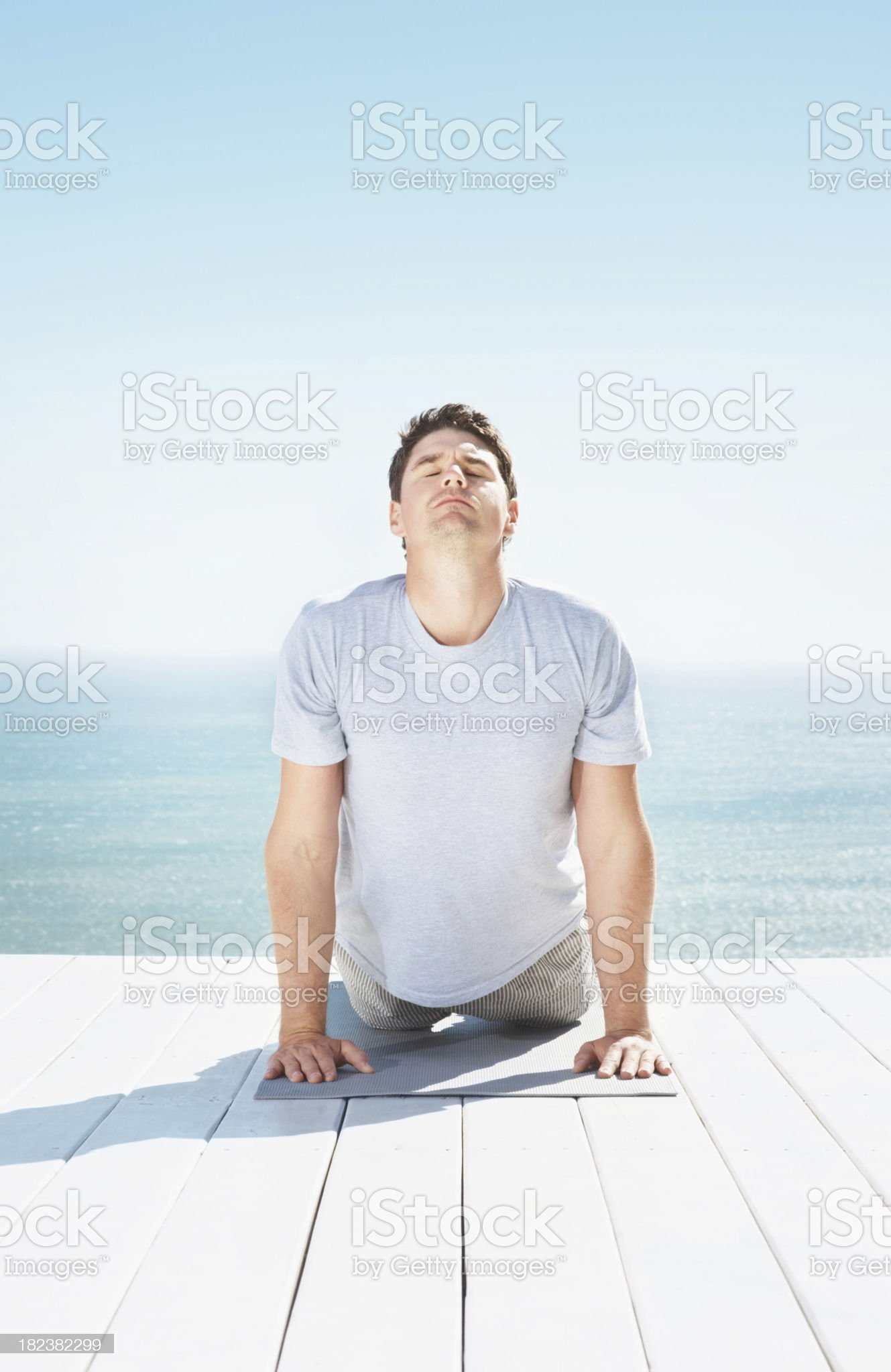 Mid adult guy doing exercise on pier royalty-free stock photo