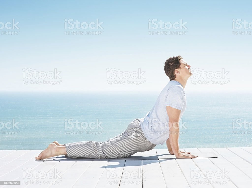 Mid adult guy practicing yoga by sea royalty-free stock photo