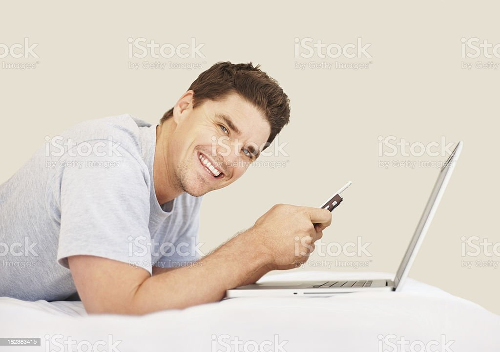 Mid adult guy text messaging on cellphone with laptop royalty-free stock photo