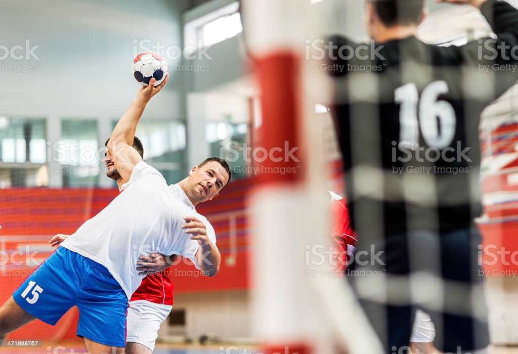 Mid adult handball player shooting at goal. stock photo
